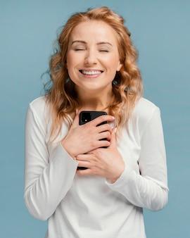 Szczęśliwa kobieta trzymając telefon komórkowy