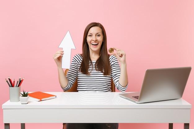 Szczęśliwa kobieta trzymająca bitcoina ze strzałką, metalową monetę w złotym kolorze, przyszła praca walutowa przy białym biurku z laptopem pc