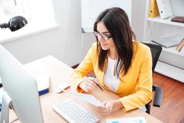 Szczęśliwa kobieta trzymająca papier i patrząca na komputer w biurze