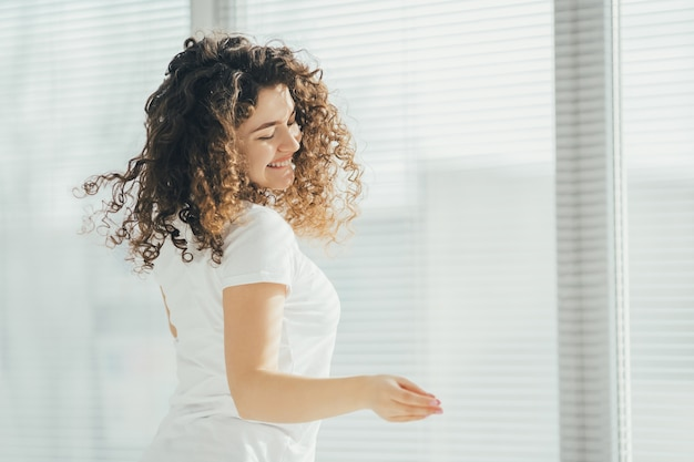 Szczęśliwa kobieta trzymająca papiery przy oknie