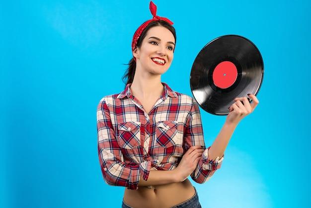 Szczęśliwa kobieta trzymająca płytę winylową na niebieskim tle