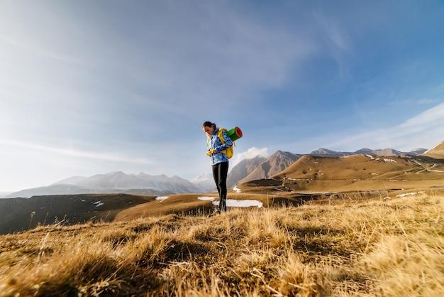Szczęśliwa kobieta turysta stojąca na tle pięknych gór