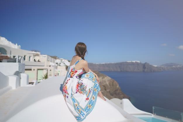 Szczęśliwa kobieta turysta w kwiatowy strój w prywatnej willi przy basenie, bielona wioska w oia, santorini, grecja. morze śródziemne.