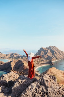 Szczęśliwa kobieta turysta w letnim kapeluszu, ciesząc się wakacjami na szczycie wzgórza