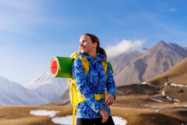 Szczęśliwa kobieta turysta w tle wysokich gór w słoneczny dzień