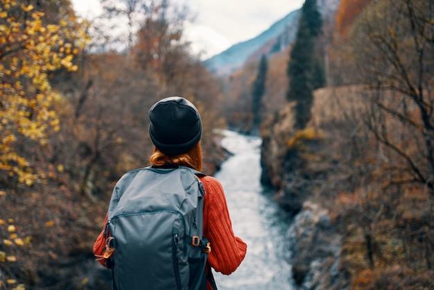 Szczęśliwa kobieta turysta z plecakiem na plecach, w pobliżu górskiej rzeki na widok natury z tyłu