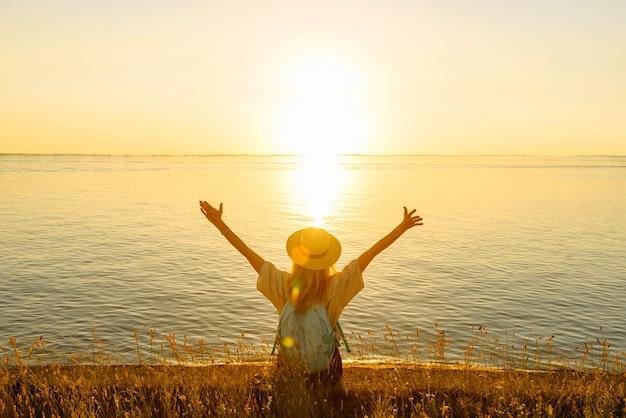 Szczęśliwa kobieta turysta z plecakiem z podniesionymi rękami siedzi nad brzegiem morza o zachodzie słońca i cieszy się pięknym widokiem. letnia koncepcja podróży i przygody.