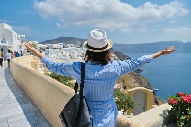 Szczęśliwa kobieta turysta z podniesionymi rękami