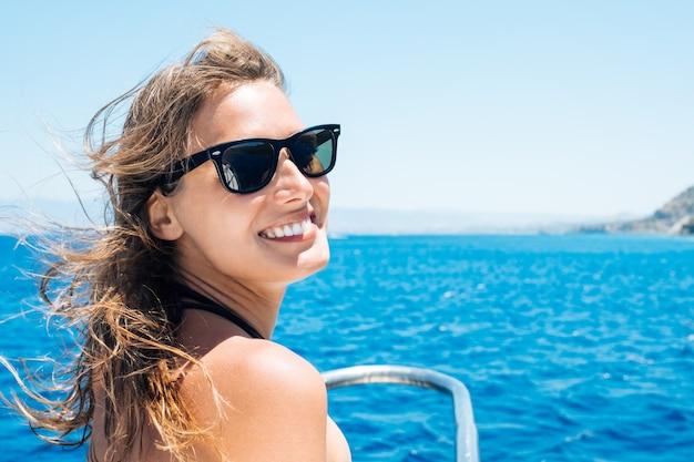 Szczęśliwa kobieta turysta, zabawy na żaglówce. letnie wakacje pod żaglami. piękna kobieta w bikini na świeżym powietrzu