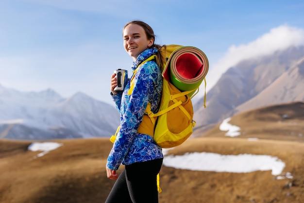 Szczęśliwa kobieta turystka w tle wysokich gór trzymająca filiżankę herbaty