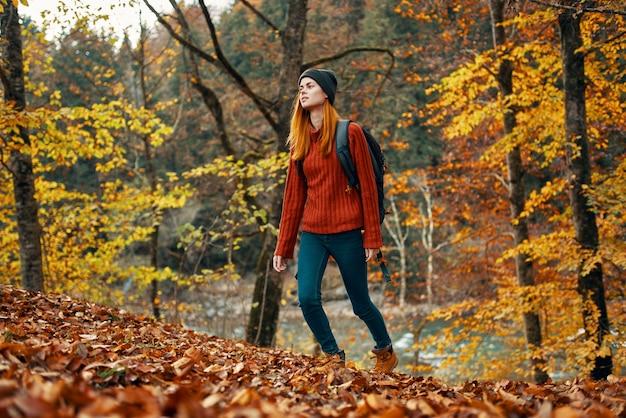 Szczęśliwa kobieta turystka z plecakiem na plecach w dżinsach i czerwonym swetrze w jesiennym leśnym parku