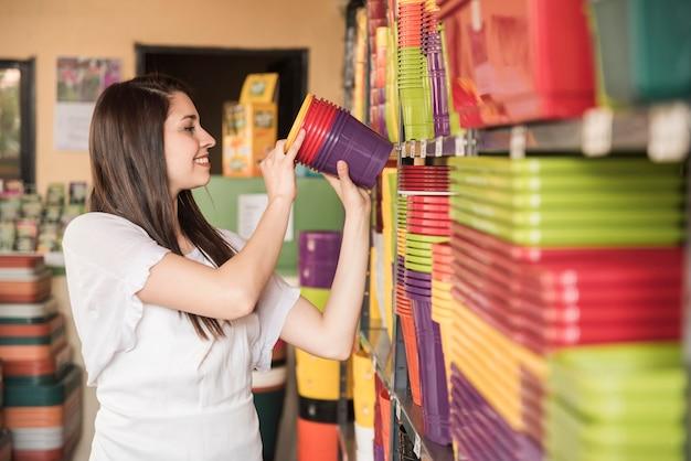 Szczęśliwa kobieta układa kolorowe kwiatonośne rośliny w półce