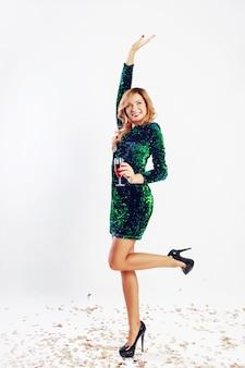 Szczęśliwa kobieta uroczystości w zielonej sukni cekinowej picia wina, ciesząc się strony. złote konfetti.