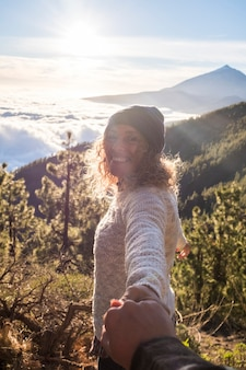 Szczęśliwa kobieta uśmiecha się i bawi się na świeżym powietrzu ze swoim chłopakiem razem w górach - pov trzymania się za ręce i miłości para, ciesząc się czasem w podróży, wakacjach lub weekendzie