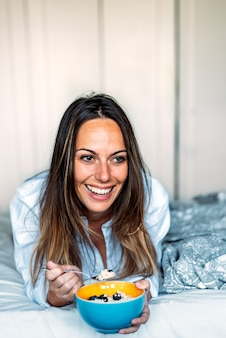 Szczęśliwa kobieta uśmiecha się i odwracając leżąc na miękkim łóżku i jedząc zdrową owsiankę