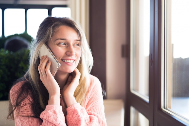 Szczęśliwa kobieta uśmiecha się i rozmawia przez telefon