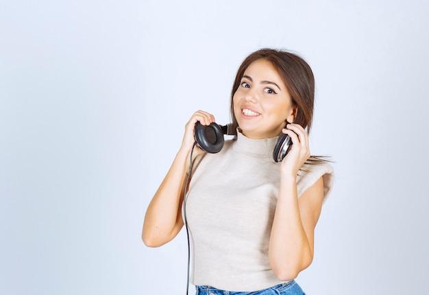 Szczęśliwa kobieta uśmiecha się i trzyma słuchawki na białym tle.