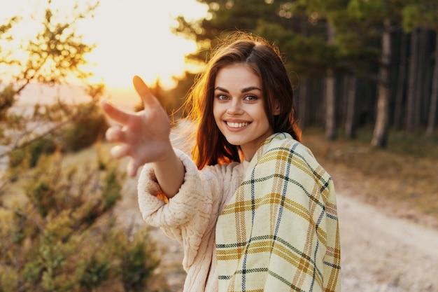 Szczęśliwa kobieta uśmiecha się w przyrodzie i wyciąga rękę do przodu zachód słońca w