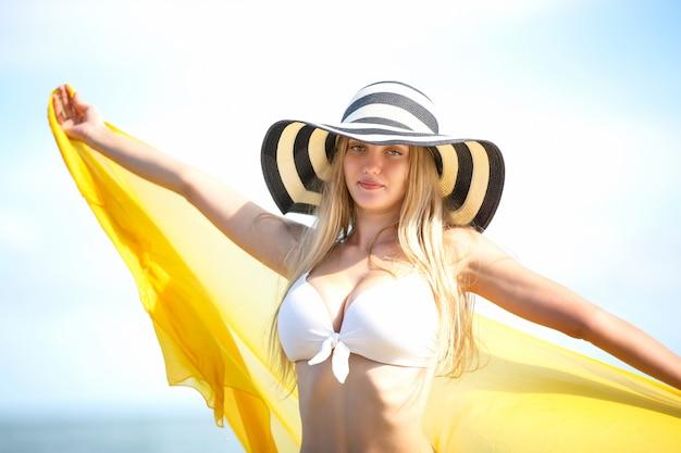 Szczęśliwa kobieta uśmiecha się zabawę i ma przy plażą. latem portret młodej pięknej dziewczyny na plaży z żółtym szalikiem i czapką.