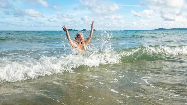 Szczęśliwa kobieta uśmiecha się zabawę i ma przy plażą. lato portret młodej pięknej dziewczyny na plaży w kapeluszu. dziewczyna się śmieje