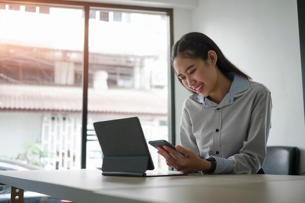 Szczęśliwa kobieta uśmiechając się i wysyłając sms-y lub masując z przyjaciółmi na telefon komórkowy w biurze.