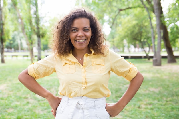 Szczęśliwa kobieta utrzymuje ręki na biodrach i pozuje przy kamerą w parku