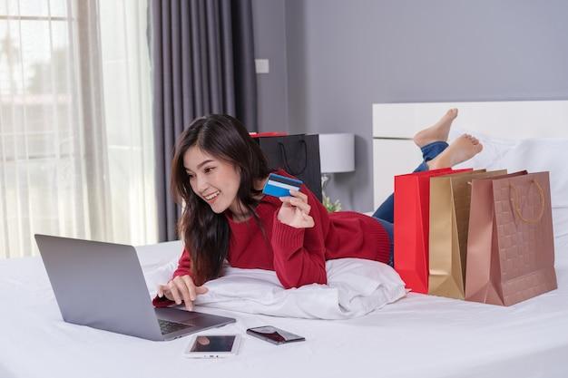 Szczęśliwa kobieta używa laptop dla online zakupy z kredytową kartą na łóżku