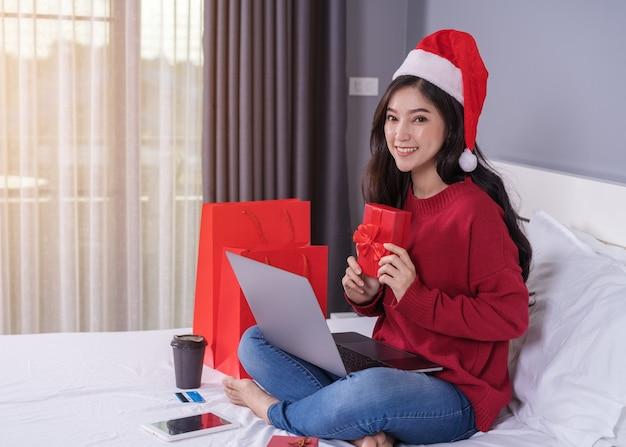 Szczęśliwa kobieta używa laptop i trzymający bożenarodzeniowego prezent na łóżku