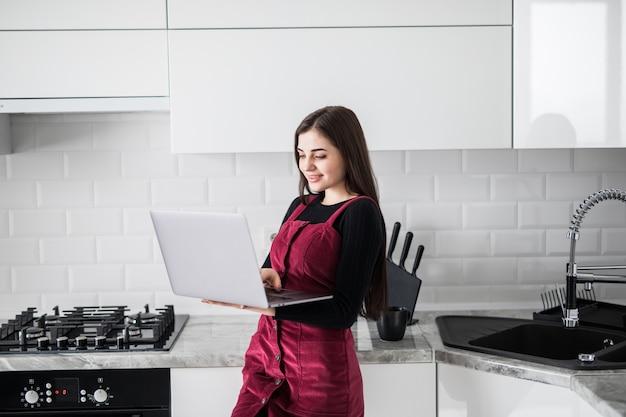 Szczęśliwa kobieta używa laptop w domu w kuchni