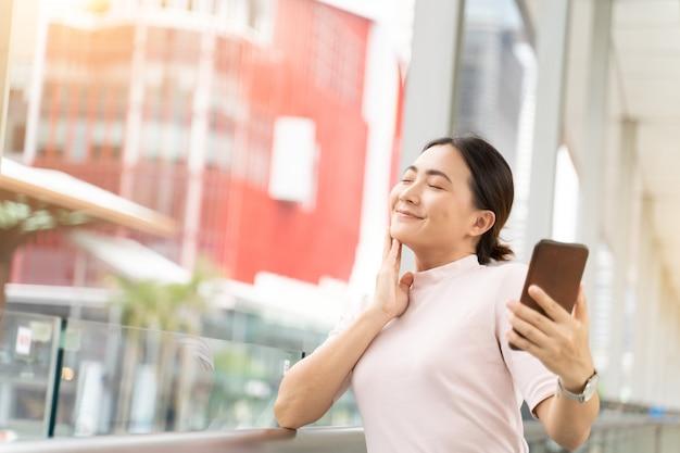 Szczęśliwa kobieta używa mądrze telefon w mieście