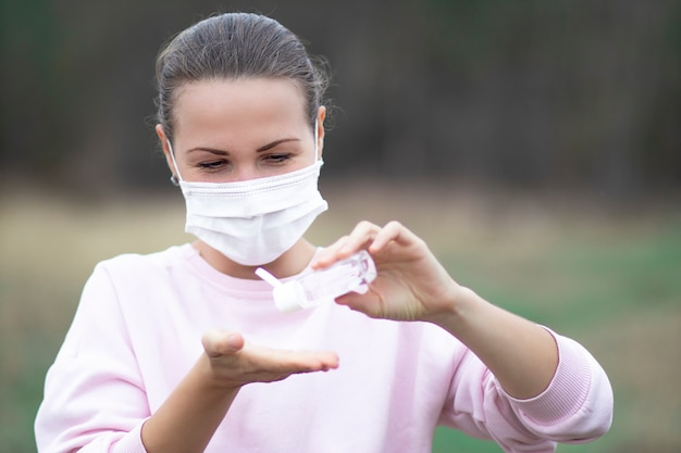 Szczęśliwa kobieta używa, stosując środek dezynfekujący z przenośnej butelki do dezynfekcji rąk, dziewczyna w masce ochronnej na twarzy. dezynfekcja, dezynfekcja rąk przeciwko koronawirusowi, bakteriom wirusowym. pandemiczny kowid-19