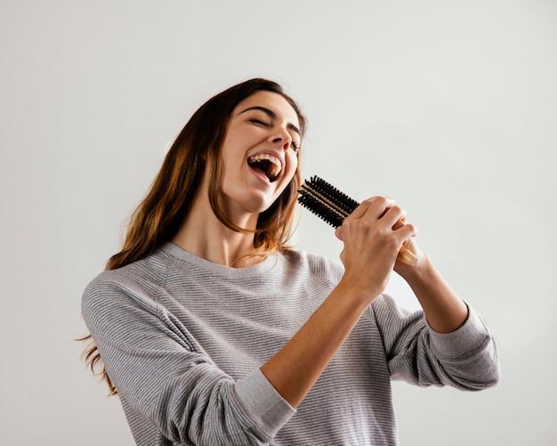 Szczęśliwa kobieta używa szczotki do włosów jako mikrofonu w domu