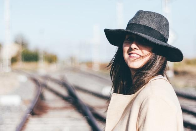 Szczęśliwa kobieta w beżowym płaszczu przeciwdeszczowym i kapeluszu na opuszczonych torach kolejowych.