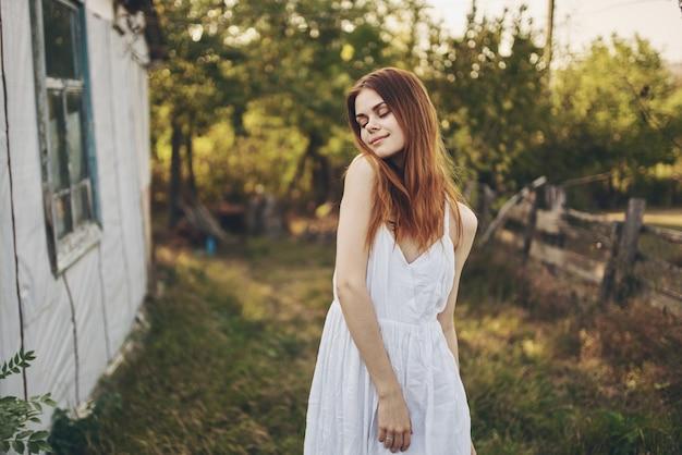 Szczęśliwa kobieta w białą sukienkę w pobliżu budynku w przyrodzie i drzew w tle.
