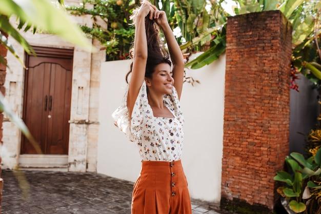 Szczęśliwa kobieta w białej bluzce i pomarańczowej spódnicy podnosi ręce
