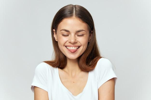 Szczęśliwa kobieta w białej koszulce śmieje się z zamkniętymi oczami i wysuwa język do przodu