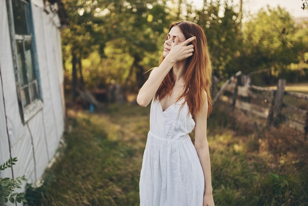 Szczęśliwa kobieta w białej sukience w pobliżu budynku w przyrodzie i drzewach.