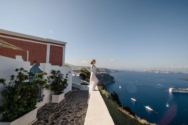 Szczęśliwa kobieta w białej sukni i słomkowym kapeluszu, ciesząc się jej wakacje na wyspie santorini. widok na morze egejskie z oia. letni cel podróży w europie. wyspy greckie