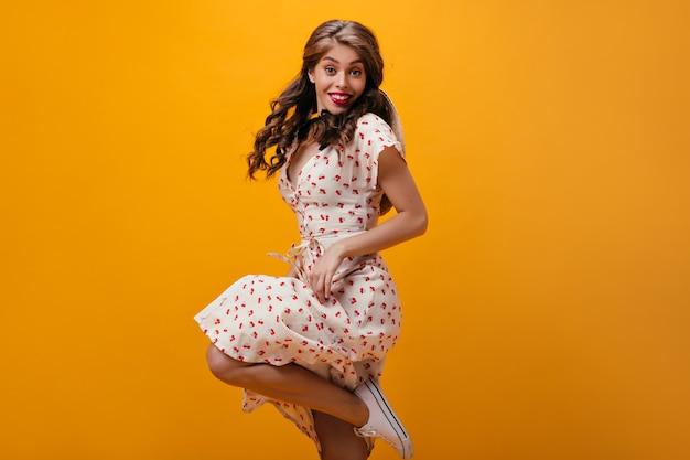 Szczęśliwa kobieta w białej sukni skacze na pomarańczowym tle. piękna stylowa dziewczyna z kręconymi włosami w letni strój i lekkie trampki, uśmiechając się.