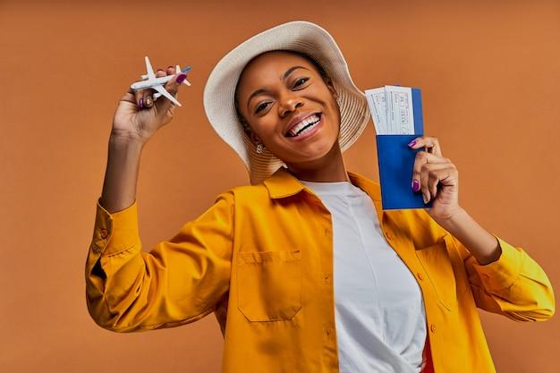 Szczęśliwa kobieta w białym kapeluszu w żółtej koszuli uśmiecha się do kamery i pokazuje zabawkowy samolot z paszportem z biletami w ręce. koncepcja podróży