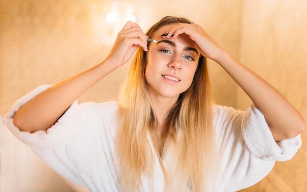 Szczęśliwa kobieta w białym szlafroku robi makijaż w łazience, pielęgnacja skóry twarzy w łazience. pielęgnacja ciała i higiena, opieka zdrowotna