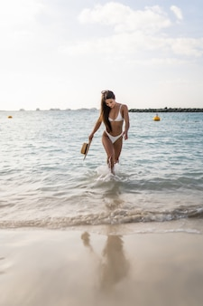Szczęśliwa kobieta w bikini i chodzenie po morzu
