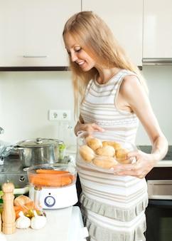Szczęśliwa kobieta w ciąży gotowania świeżych warzyw z parowcem w kuchni