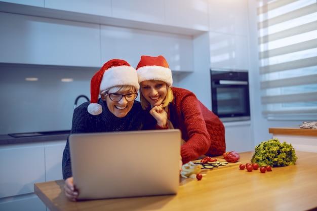 Szczęśliwa kobieta w ciąży i jej matka, opierając się na blacie kuchennym i patrząc przepis na laptopie na zdrowy świąteczny obiad. oboje mają na głowach czapki mikołaja. na blacie kuchennym są różnego rodzaju warzywa.