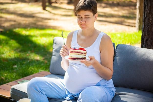 Szczęśliwa kobieta w ciąży jedzenie słodkie ciasto w lato park