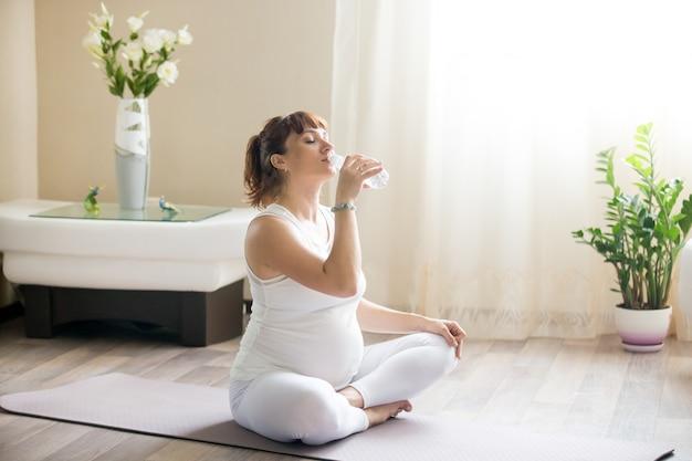 Szczęśliwa kobieta w ciąży pije wodę naturalną po wypracowaniu