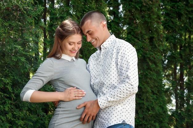 Szczęśliwa kobieta w ciąży, rodzinna para w parku