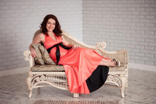 Szczęśliwa kobieta w ciąży uśmiecha się i przytula brzuch.