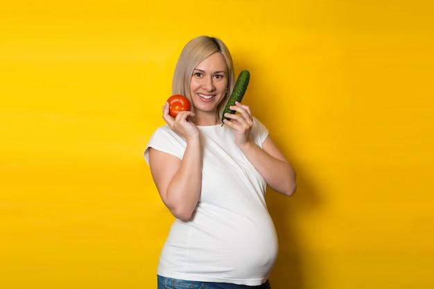 Szczęśliwa kobieta w ciąży wybiera pigułki i warzywa na żółtej ścianie. odżywianie i dieta podczas ciąży