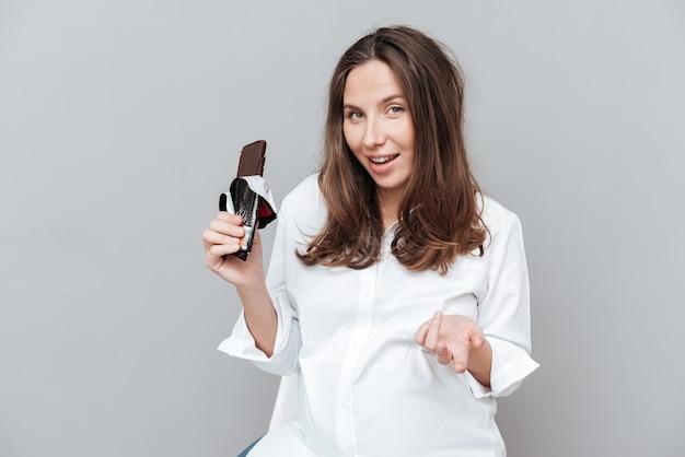 Szczęśliwa kobieta w ciąży z czekoladą patrząc na kamerę